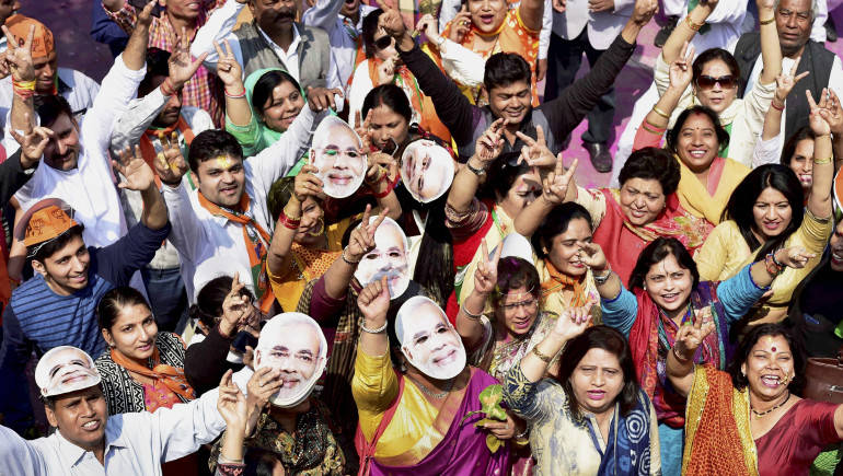 New Delhi: BJP workers and supporters, wearing the mask of Prime Minister Narendra Modi, celebrate the party's victory in the assembly elections, at party headquarters in New Delhi on Saturday. PTI Photo