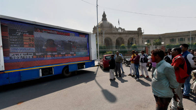 Lucknow: People watching Assembly election results on a giant screen fixed at a mobile van outside the Vidhan Sabha, in Lucknow on Saturday. PTI Photo