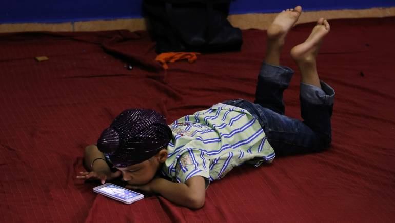 A young boy plays with a smartphone (Representative image from Reuters)