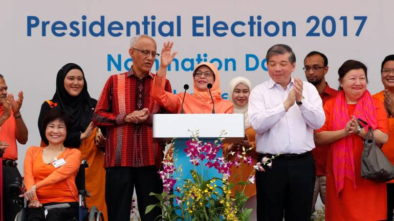 Singapore's President-elect Halimah Yacob addresses supporters beside her husband Mohammed Abdullah Alhabshee before leaving the nomination centre in Singapore