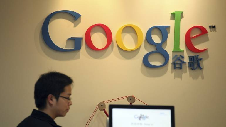 A worker at Google in Shanghai walks near their reception desk in their Shanghai office