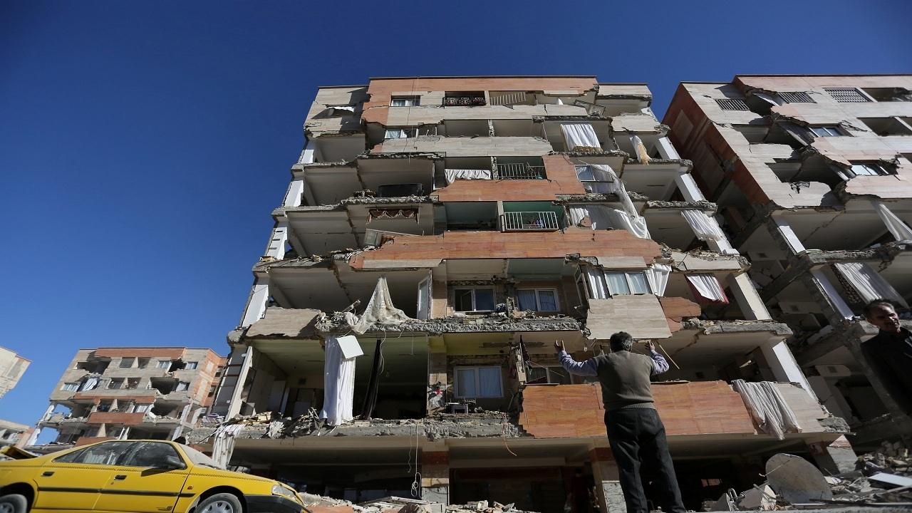 An onlooker looks at a building damaged by an earthquake in Sarpol-e Zahab county in Iran.
