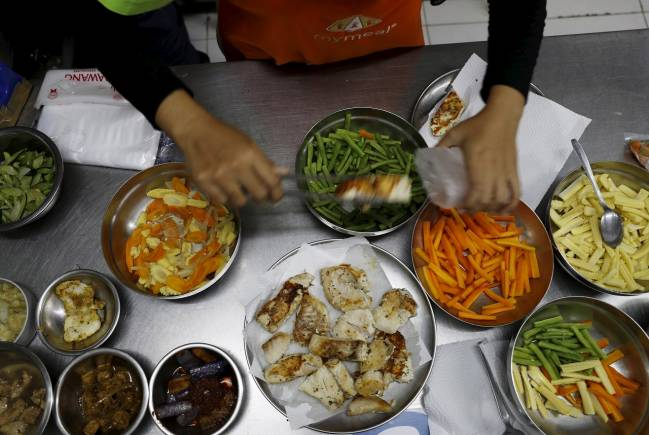 A worker of MyMeals, a food delivery service, prepares dinner for people with diabetes at Cikokol district near Jakarta, Indonesia, April 25, 2016. REUTERS/Beawiharta - GF10000397108