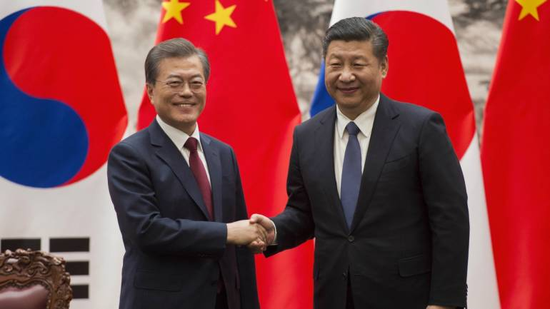 South Korean President Moon Jae-in, left, and Chinese President Xi Jinping shake hands at the end of a signing ceremony at the Great Hall of the People in Beijing. (PTI)