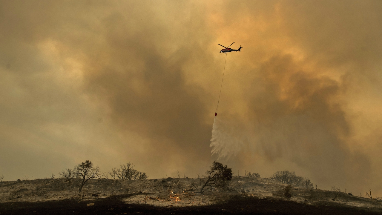 A helicopter drops water while trying to keep a wildfire from jumping Santa Ana Road near Ventura. (PTI)