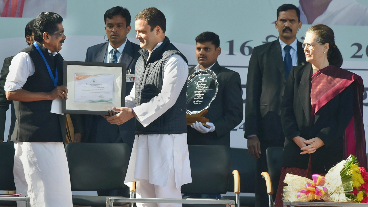 Congress' central election authority (CEA) chairman Mullappally Ramachandran hands over Rahul Gandhi the certificate of his elevation to the top post during a grand event held in presence of his mother and predecessor Sonia Gandhi, in New Delhi. (PTI)