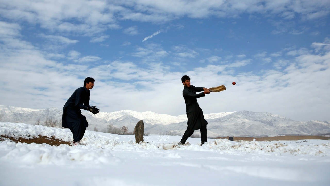 Afghan men play cricket on a field covered in snow on the outskirts of Kabul. (Reuters)
