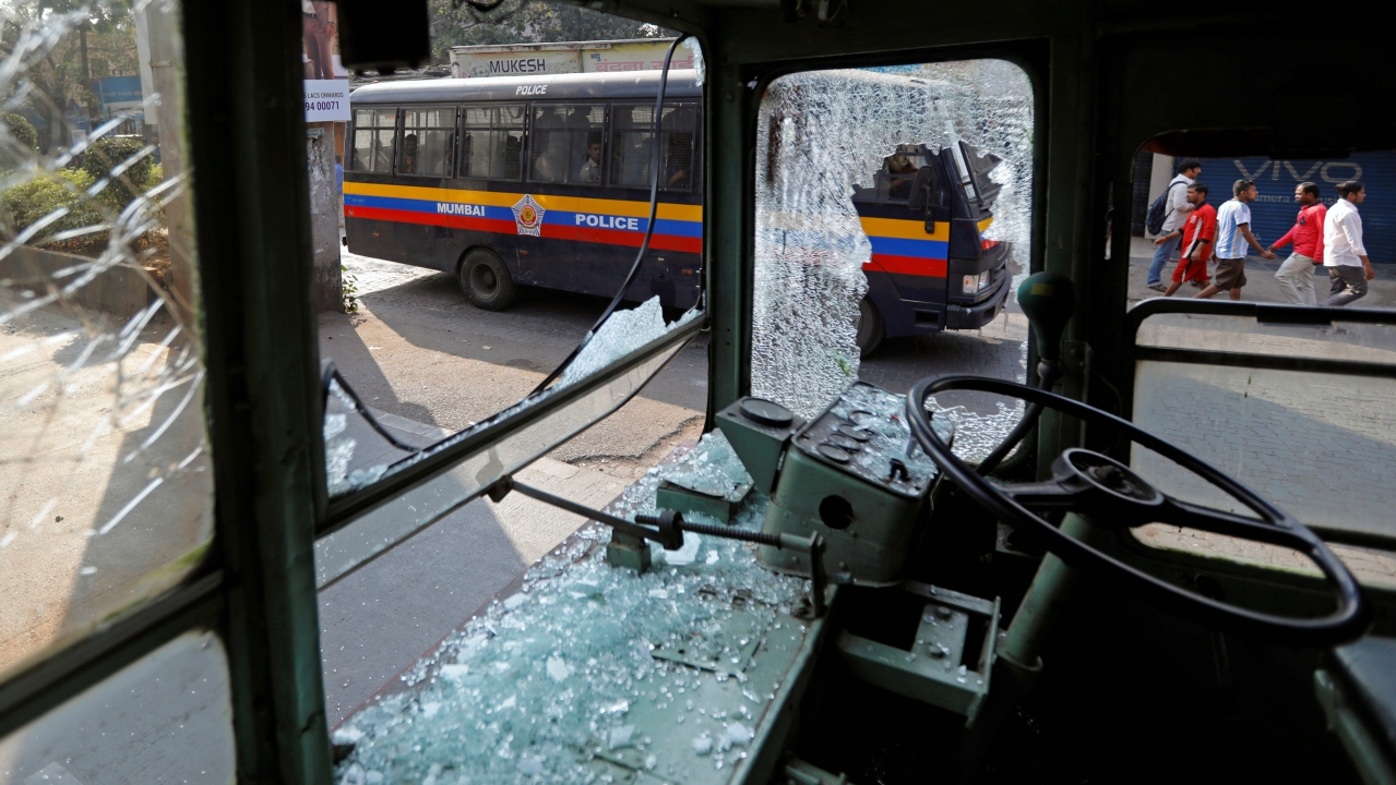A police van carrying personnel drives past a damaged public bus during a protest in Mumbai. (Reuters)