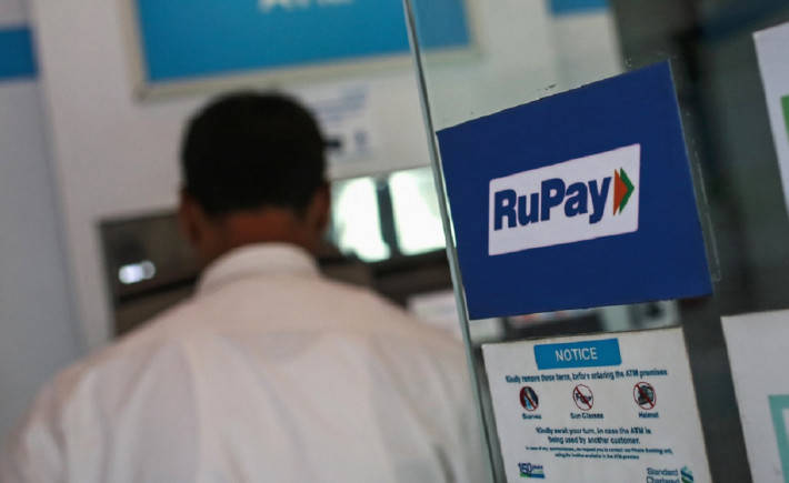A RuPay sign is seen on the door of an ATM while a user is seen, at a commercial building in Mumbai, September 2014 (REUTERS/Danish Siddiqui)