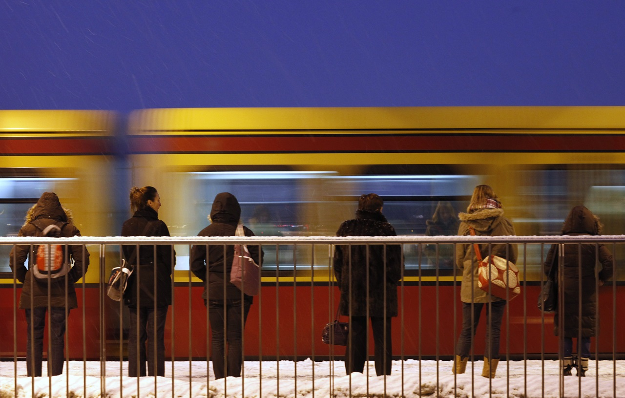 Passengers wait on the platform for a S-Bahn commuter train on a snowy morning in Berlin January 4, 2011. REUTERS/Thomas Peter (GERMANY - Tags: TRANSPORT ENVIRONMENT) - BM2E7140RMI01