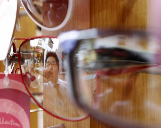 Sales clerk Satoshi Watanabe is reflected in a pair of glasses as he performs a rap song in front an optical store in a shopping district of Tokyo February 24, 2011. Watanabe began rapping four years ago at different branches of the eyeglass chain store he works at after a manager suggested he try new ways to boost sales. According to Watanabe, the act managed to improve sales initially and he has managed to retain a few loyal customers who remember his act. REUTERS/Kim Kyung-Hoon (JAPAN - Tags: SOCIETY EMPLOYMENT BUSINESS ODDLY) - GM1E72O1ORC01