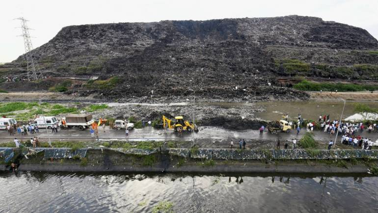 Rescue and relief operations underway after a part of the Ghazipur garbage landfill collapsed in east Delhi on September 01, 2017. Several people and a vehicle were swept into the canal after the mishap. (PTI)