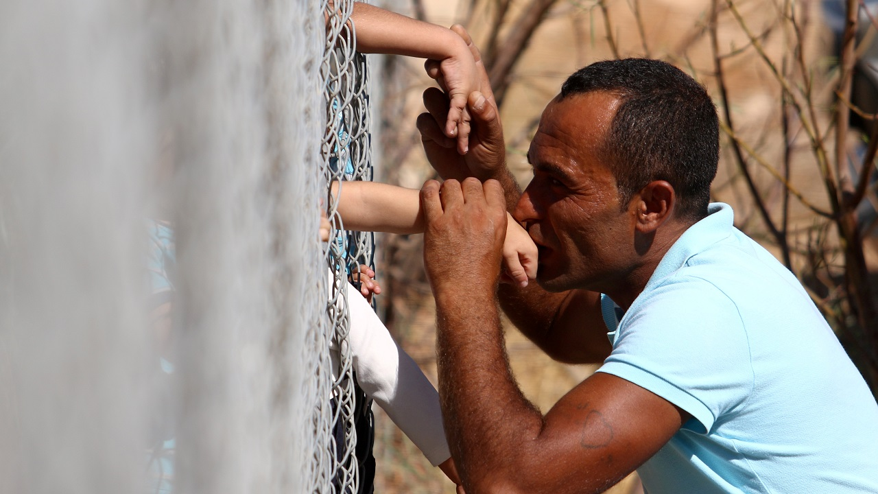 Ammar Hammasho from Syria who lives in Cyprus kisses his children who arrived at the refugee camp in Kokkinotrimithia outside Nicosia, Cyprus on September 10, 2017. (Reuters)