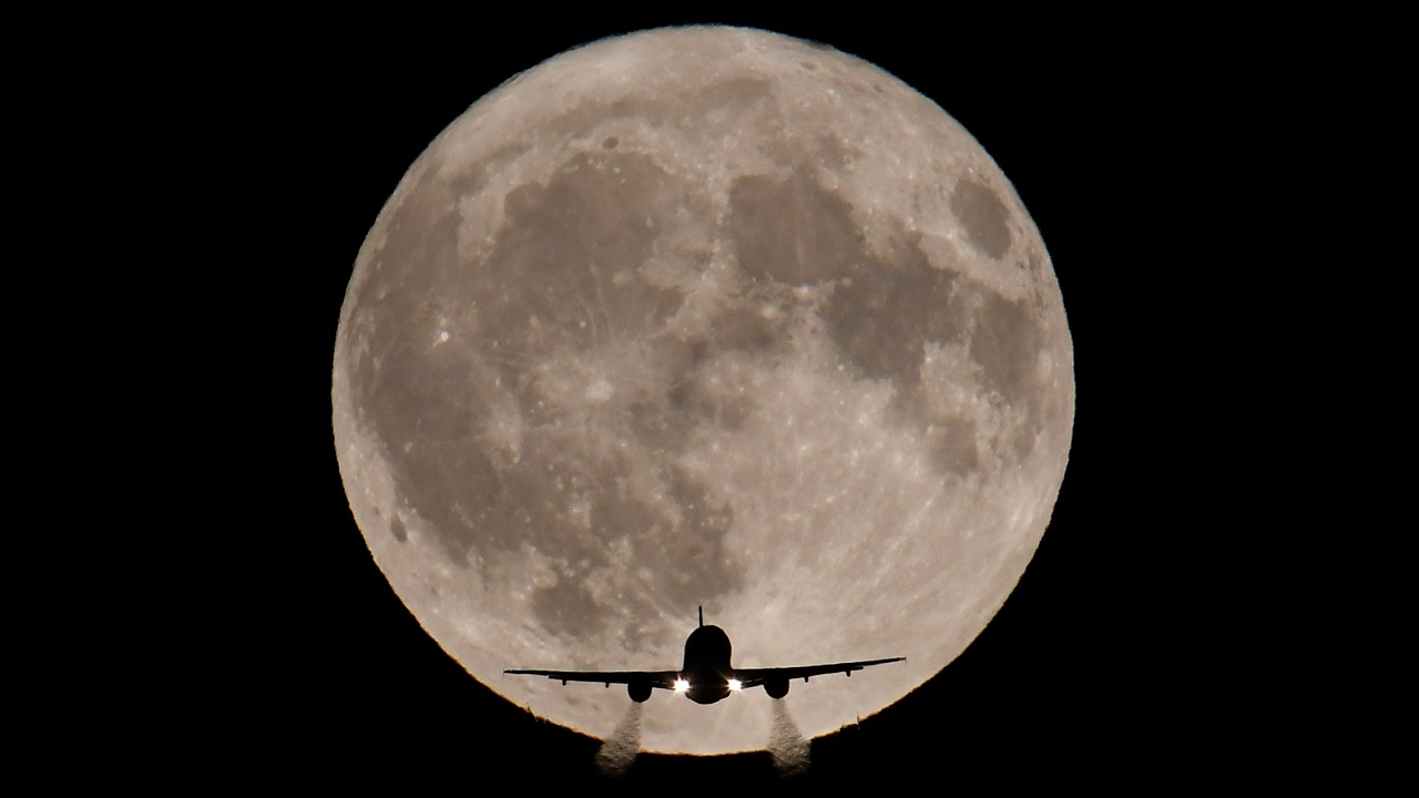 A passenger plane, with a full Harvest moon seen behind, makes its final landing approach towards Heathrow Airport in London, Britain on October 5, 2017. (Reuters)
