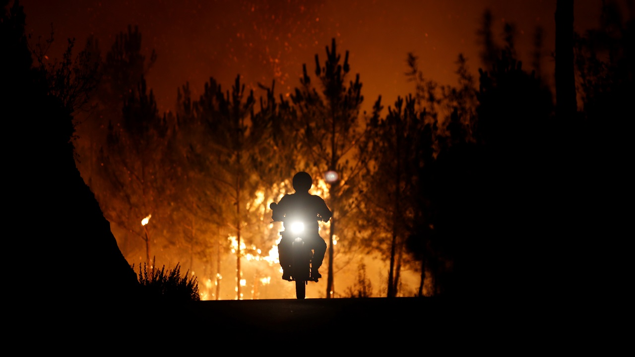 A firefighter is riding a motorbike away from a forest fire next to the village of Macao, near Castelo Branco, Portugal on July 26, 2017. (Reuters)