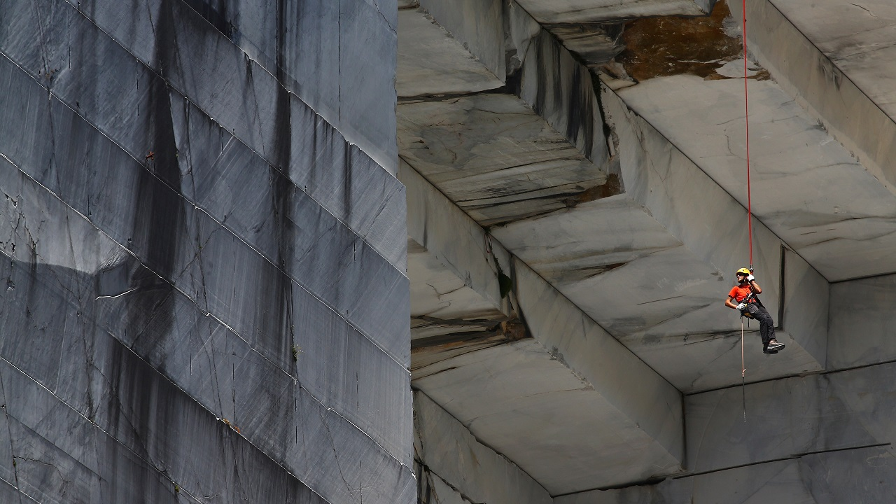 "A worker, known as a ""Tecchiaiolo"", examines marble at the Cervaiole quarry on Monte Altissimo in the Apuan Alps, Tuscany, Italy on July 18, 2017. (Reuters)"