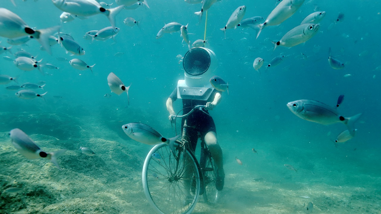 A woman dives and pretends to ride a bike in Underwater Park in Pula, Croatia on August 1, 2017. (Reuters)