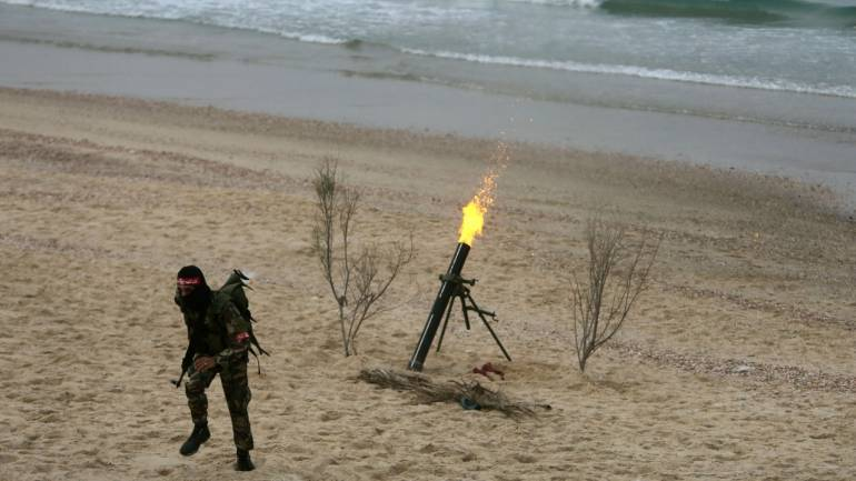 A Palestinian militant of the Popular Front for the Liberation of Palestine (PFLP) fires a mortar shell during a military exercise in front of the media, on beach in the southern Gaza Strip (REUTERS)