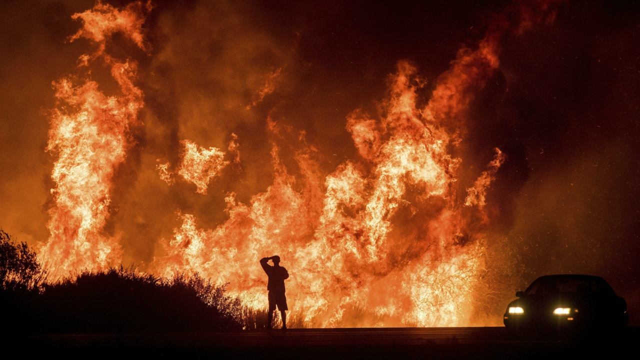 A motorists on Highway 101 watches flames from the Thomas fire leap above the roadway north of Ventura, California. As many as five fires have closed highways, schools and museums, shut down production of TV series and cast a hazardous haze over the region. About 200,000 people were under evacuation orders. No deaths and only a few injuries were reported. (PTI)