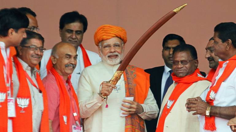 Prime Minister Narendra Modi being presented a sword by the supporters during an election campaign rally, at Dhandhuka village of Ahmedabad district on Wednesday. (PTI)
