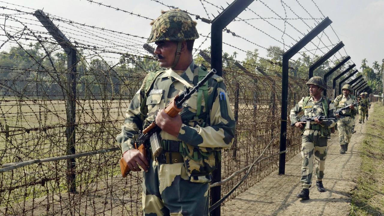 Border Security Force (BSF) personnel patrol along the India-Bangladesh border fence at Yakub Nagar village ahead of Republic Day in Dharmanagar, Tripura (PTI)