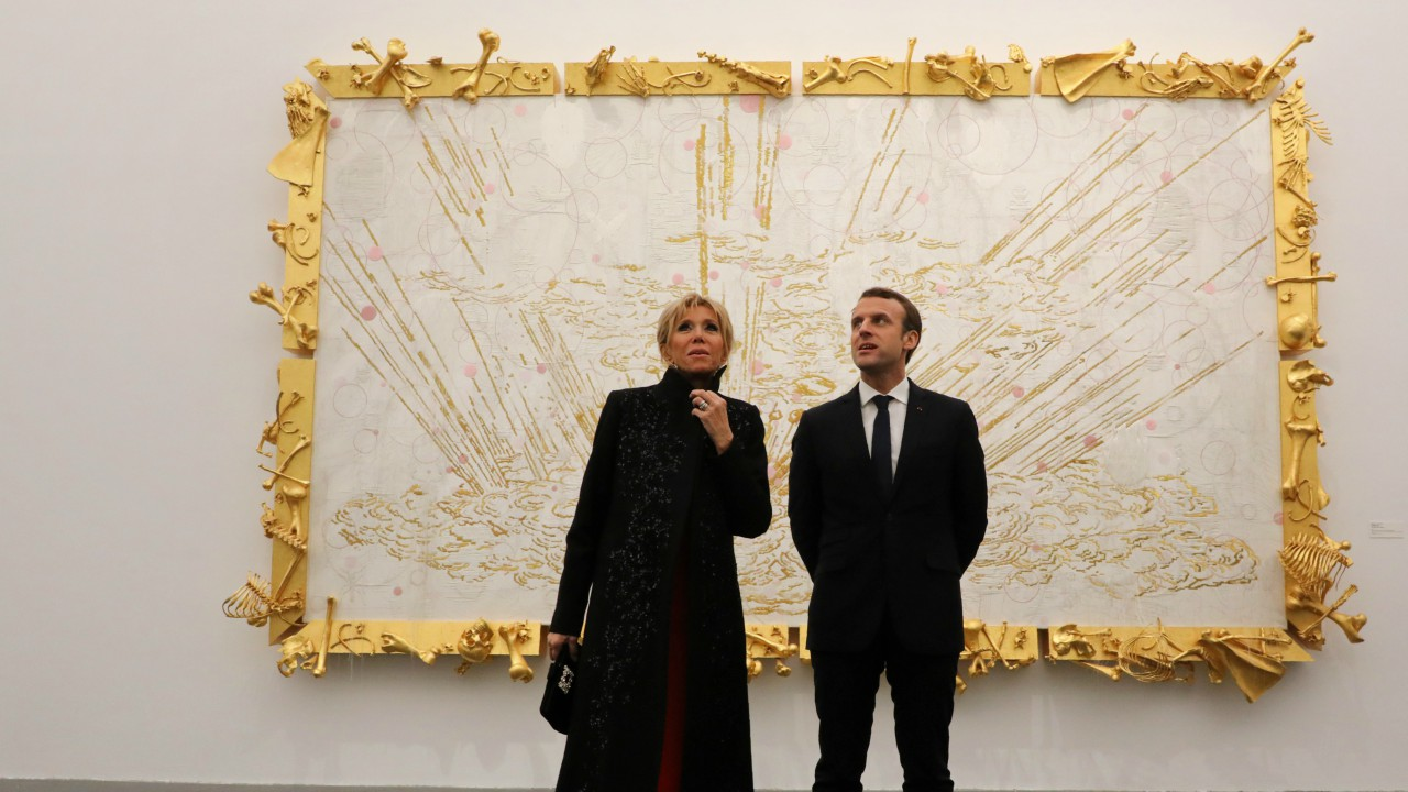 French President Emmanuel Macron (R) and his wife Brigitte Macron (L) look at artwork during a visit to the Ullens Chinese Contemporary Art Centre in Beijing. (REUTERS)
