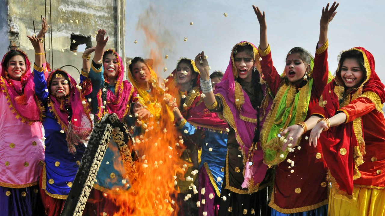 Women, dressed in their traditional Punjabi, attire fly kites as they celebrate the festival of Lohri in Amritsar. (PTI)