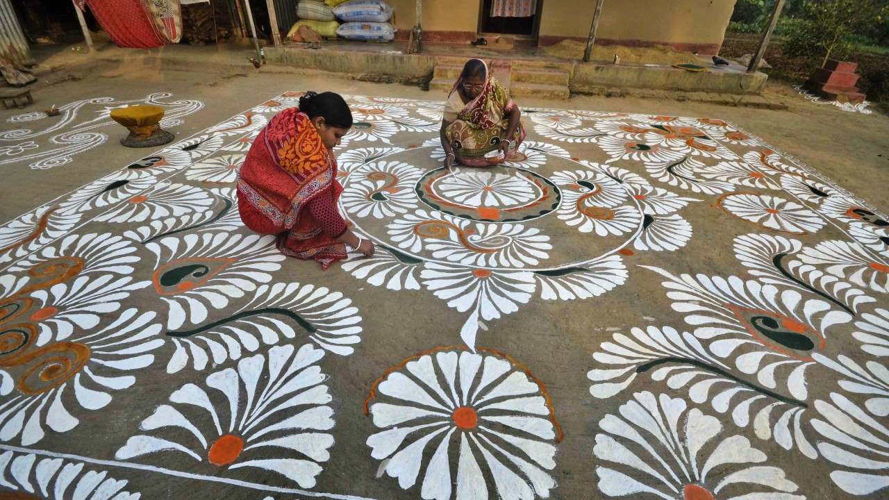 Women making a 'Rangoli' in front of their house on the eve of the Makar Sankaranti festival in a village on the outskirts of Agartala  (PTI)
