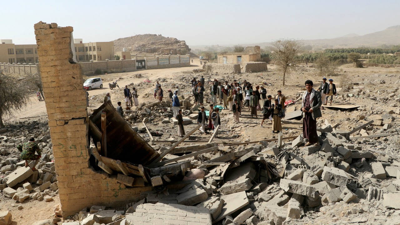 People gather at the site of an air strike that destroyed a house on the outskirts of the northwestern city of Saada, Yemen. (REUTERS)