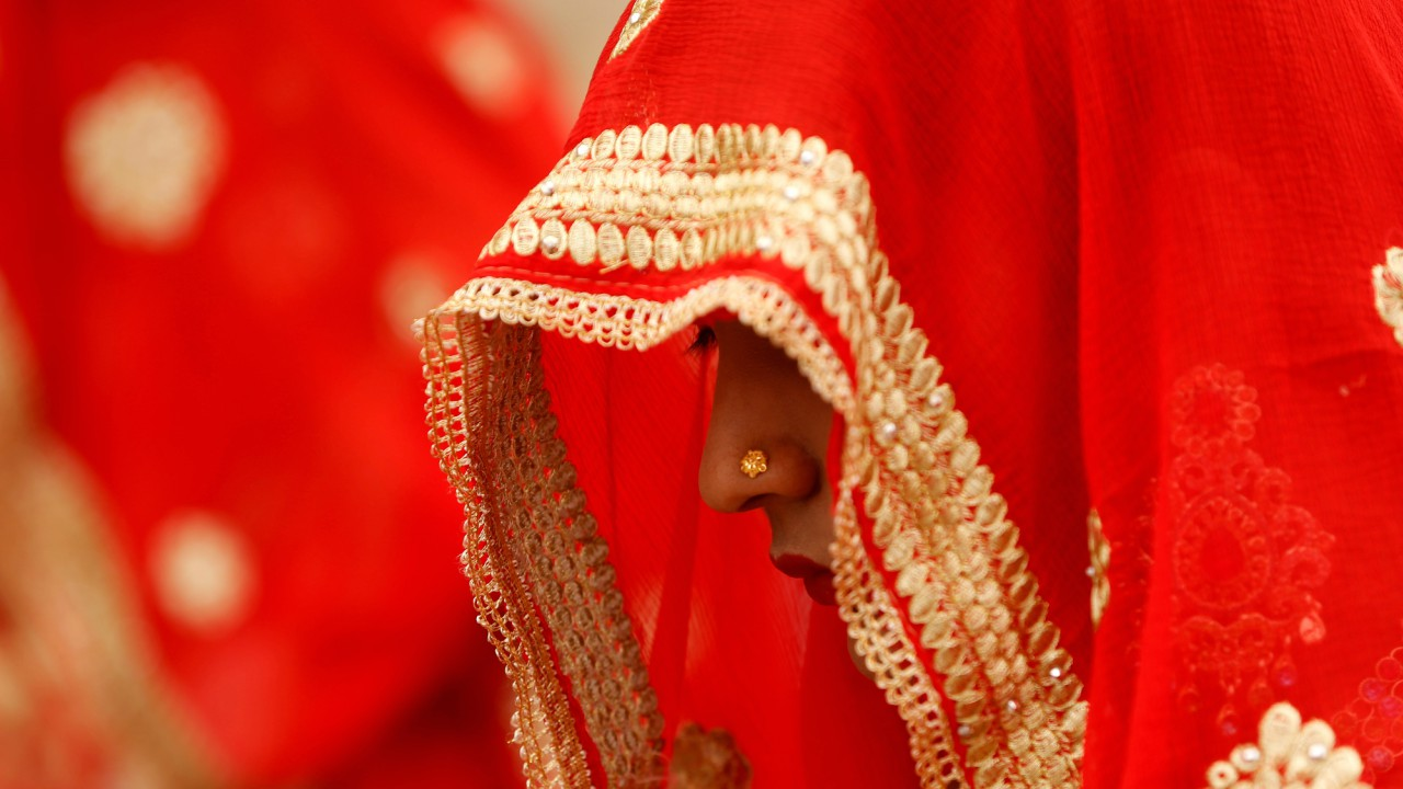 A bride waits to take her wedding vows during a mass marriage ceremony in which, according to its organisers, 111 Muslim couples took their wedding vows, at a mosque in Ahmedabad. (REUTERS)
