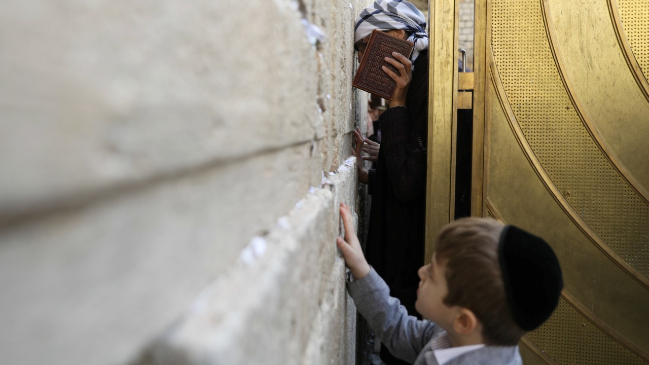 A child touches the Western Wall, Judaism's holiest prayer site, as a woman prays in the women's section of the site, in Jerusalem's Old City. (REUTERS)