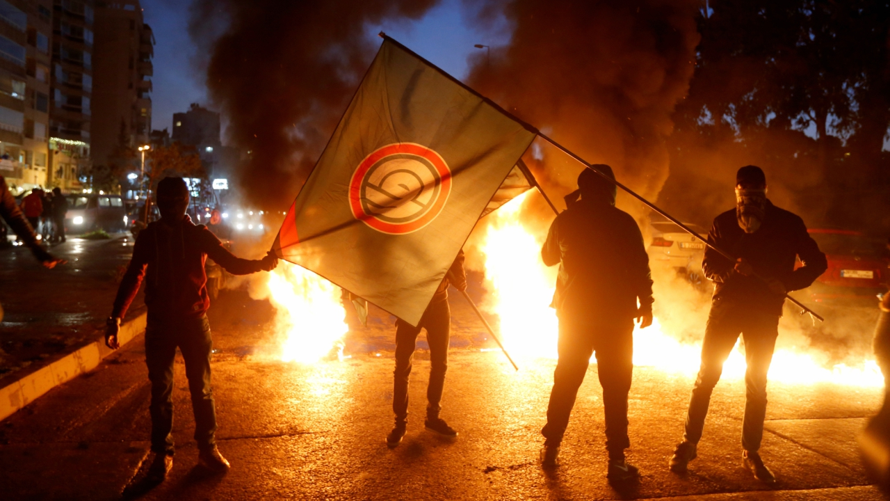 Supporters of Amal movement hold the party's flag near burning tires in Beirut, Lebanon  (REUTERS)