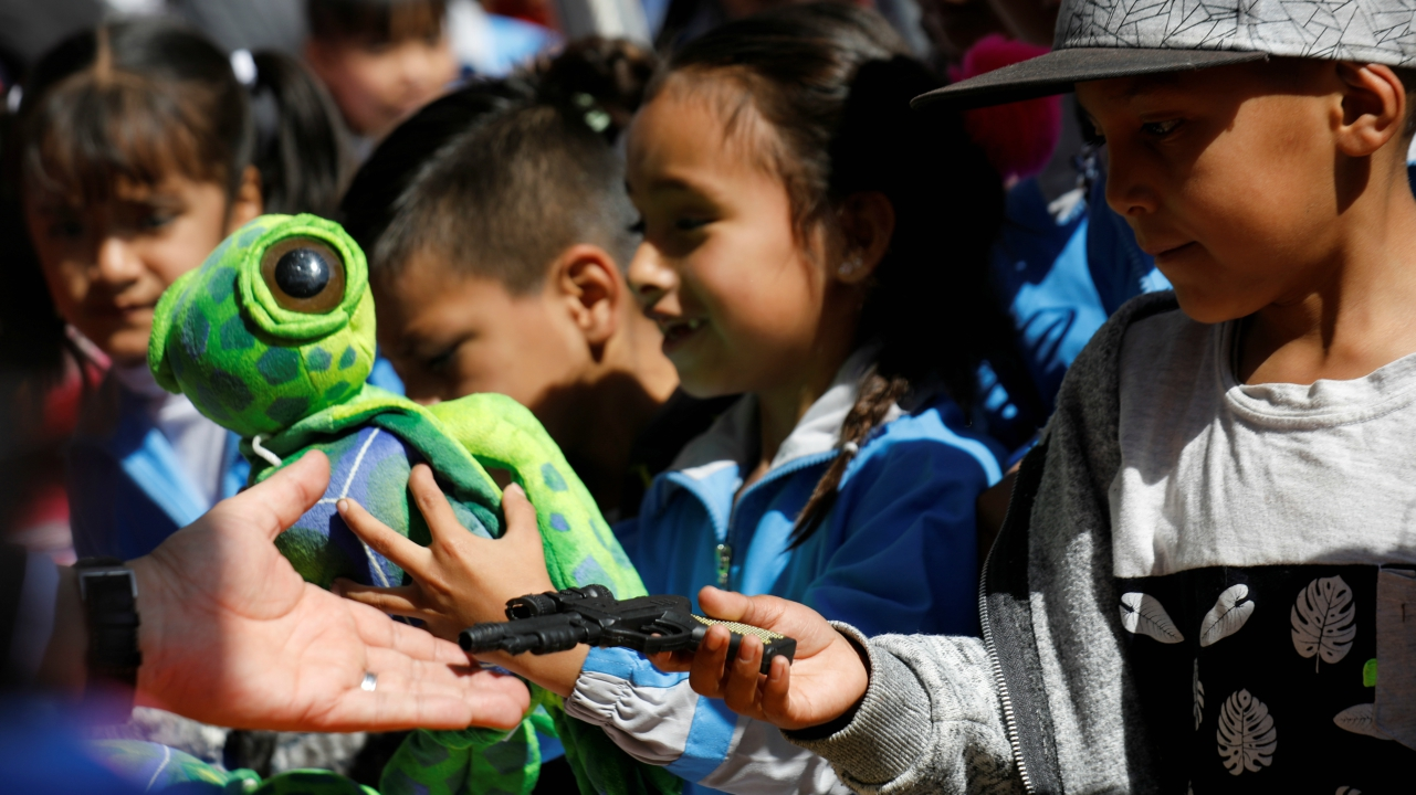 7. A child exchanges a toy gun during a voluntary disarming program run by the government with the support of the Army and the Catholic Church, which aims to swap toy weapons for fluffy toys outside the Metropolitan Cathedral in Mexico City, Mexico. (REUTERS)