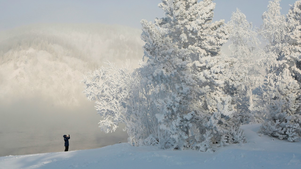 A woman takes pictures on a bank of the Yenisei River covered with snow and hoarfrost, with the air temperature at about minus 34 degrees Celsius (minus 29.2 degrees Fahrenheit), outside Krasnoyarsk, Russia. (REUTERS)