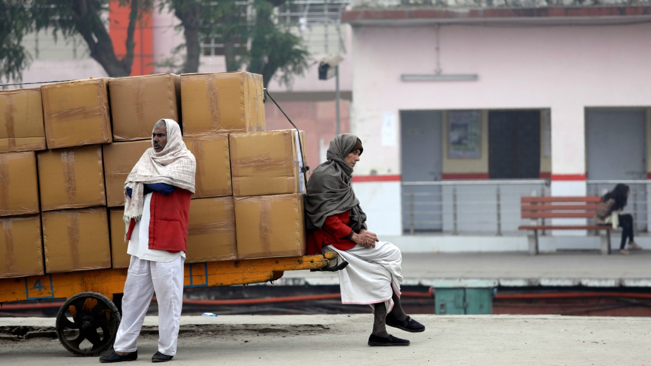A porter wrapped in a shawl sits on a handcart loaded with goods at a railway platform on a cold winter morning in New Delhi, India (REUTERS)