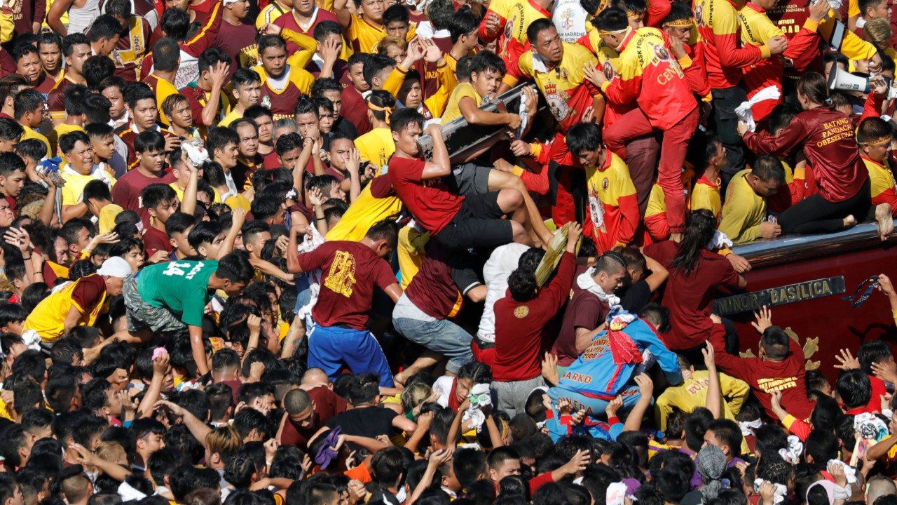 Catholic devotees try to climb the carriage of the black Nazarene during the day long procession at Roxas Boulevard, Manila, Philippines. (REUTERS)