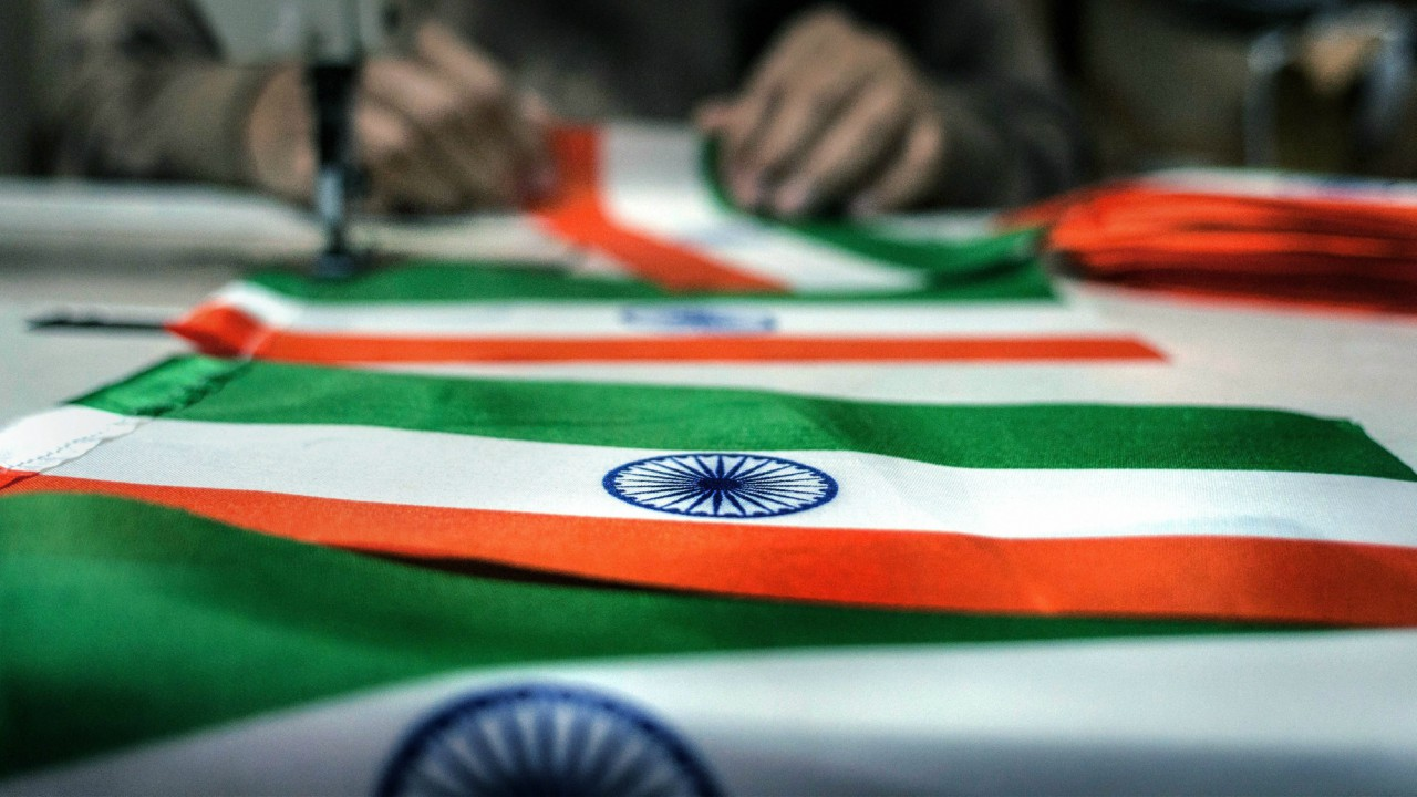 A tailors stitches together a national flag at his workshop ahead of Republic Day, in New Delhi on Monday. (PTI)