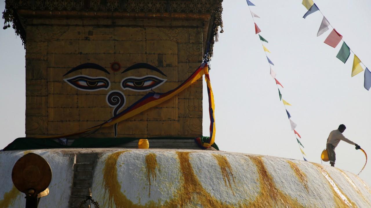 A man splashes paint on the dome of Swayambhunath Stupa in Kathmandu, Nepal. (REUTERS)