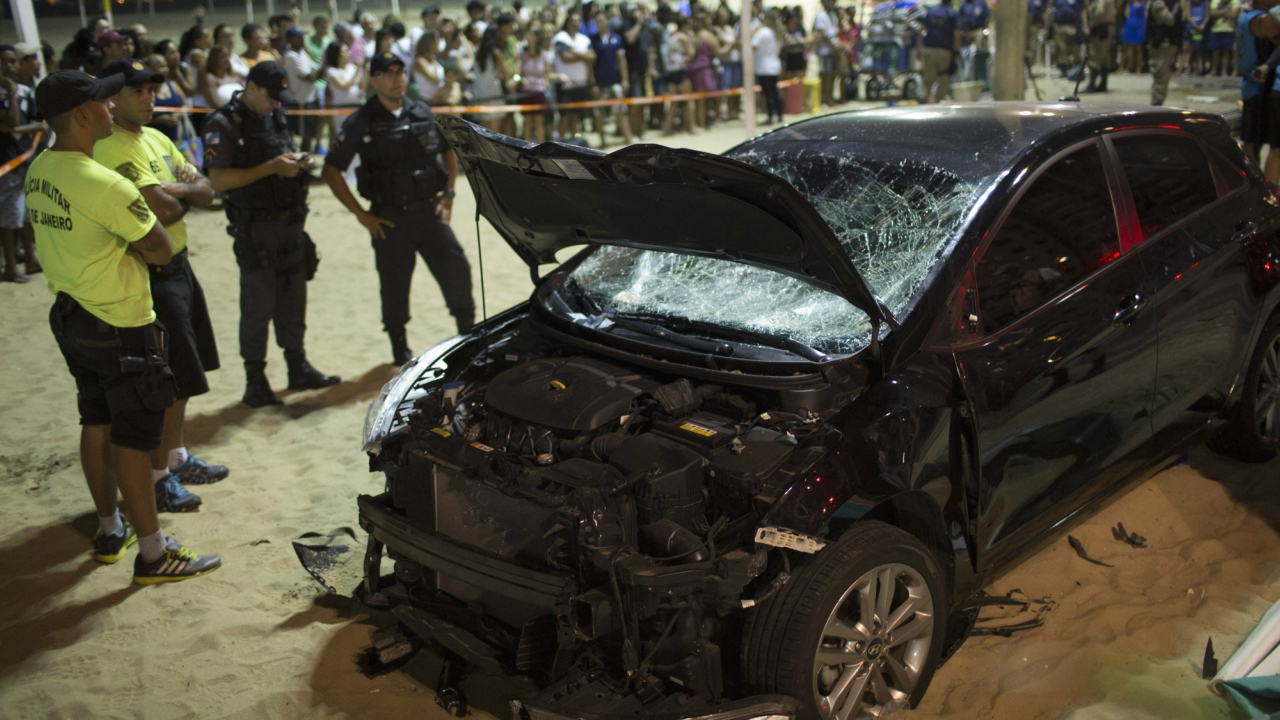 Police officers stand next to the a car that has driven into the crowded seaside boardwalk along Copacabana beach in Rio de Janeiro, Brazil. (AP/PTI)