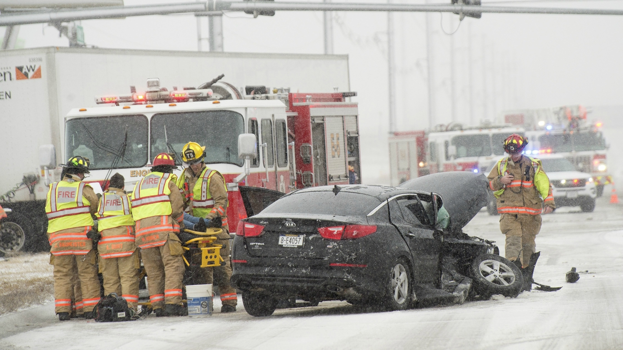 Firefighters tend to a victim at the scene of a crash accident in Lincoln, as driving conditions deteriorated during a winter storm. (AP/PTI)