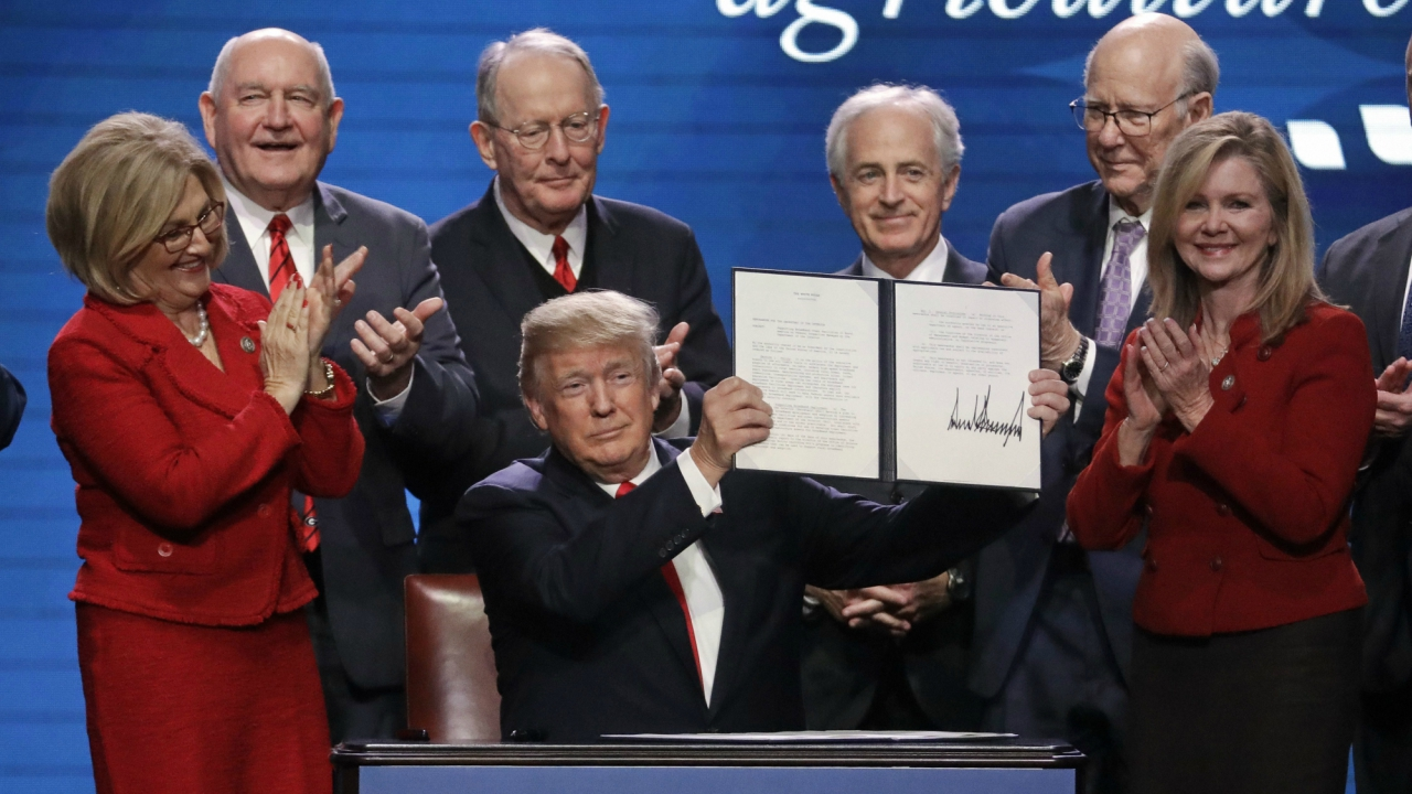 President Donald Trump holds up an executive order after signing it at the American Farm Bureau Federation annual convention on Monday. (Reuters)