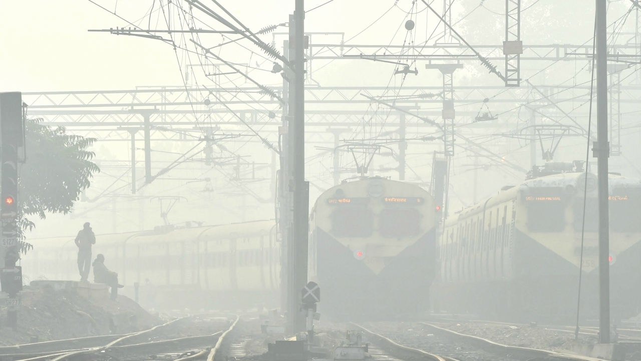 Trains run slowly as fog envelopes a railway track in New Delhi on Monday. Normal life was affected across North India with many trains and flights delayed due to cold weather and fog. (PTI)