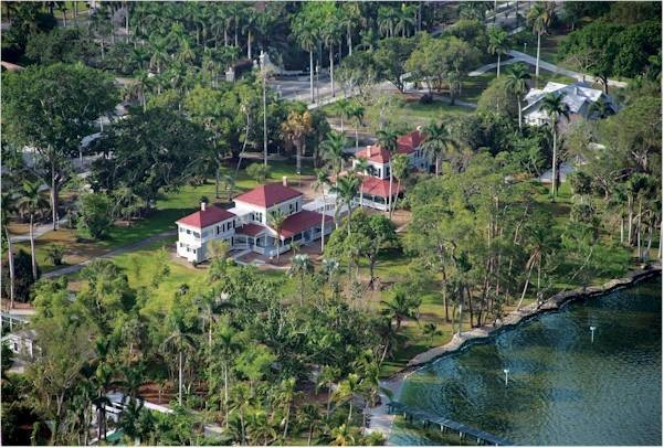 This estate in Florida is adjacent to the winter homes of Thomas Edison and another person, who set it up together. It consists of the first tree of a particular species to be planted in USA, in an attempt to find a more cost-effective way to produce rubber for tires. The tree was introduced to the two by a mutual friend who too had interests in finding a solution to the rising cost of rubber. The tree's name comes from a certain community in India, where early travelling businessmen belonging to that community sat under the tree for to take rest. Who are the two men and which tree?
