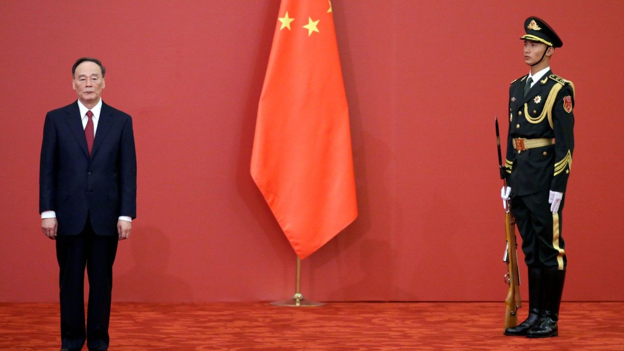 Former China's Politburo Standing Committee member Wang Qishan stands next to a Chinese flag at the Great Hall of the People in Beijing, China (REUTERS)
