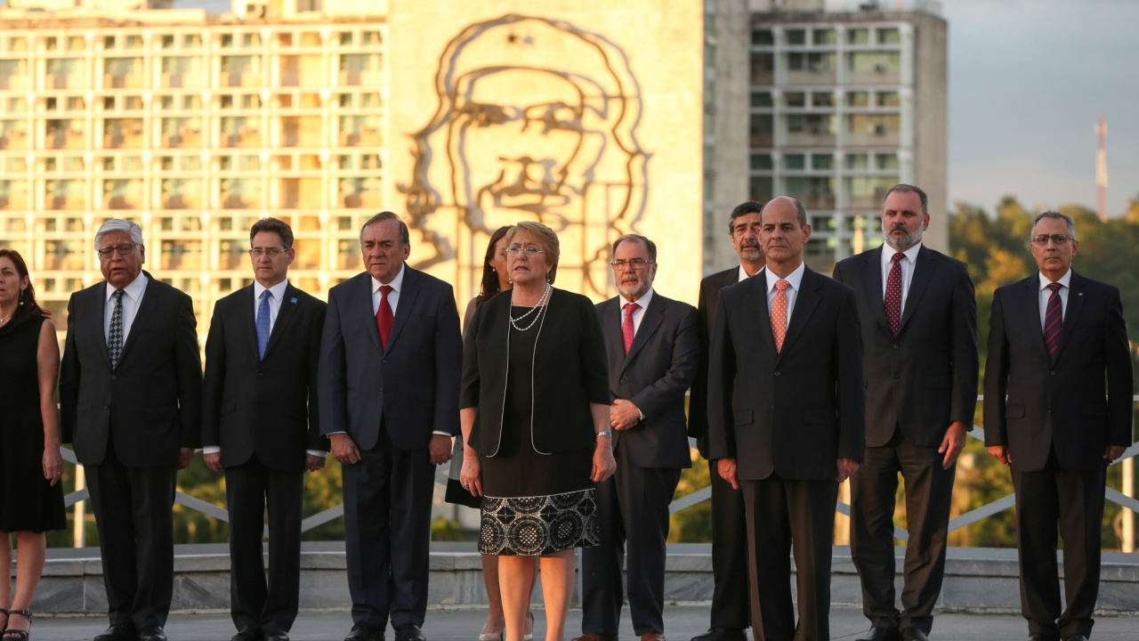 """Chile's President Michelle Bachelet (C) stands near an image of late revolutionary hero Ernesto """"Che"""" Guevara (background) during a wreath-laying ceremony at the Jose Marti monument at Revolutionary Square in Havana, Cuba. (Reuters)"""