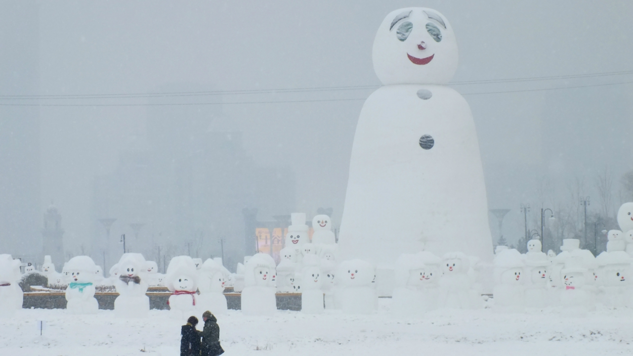 People are seen next to a giant snowman at a park in Harbin, Heilongjiang province, China. (Reuters)