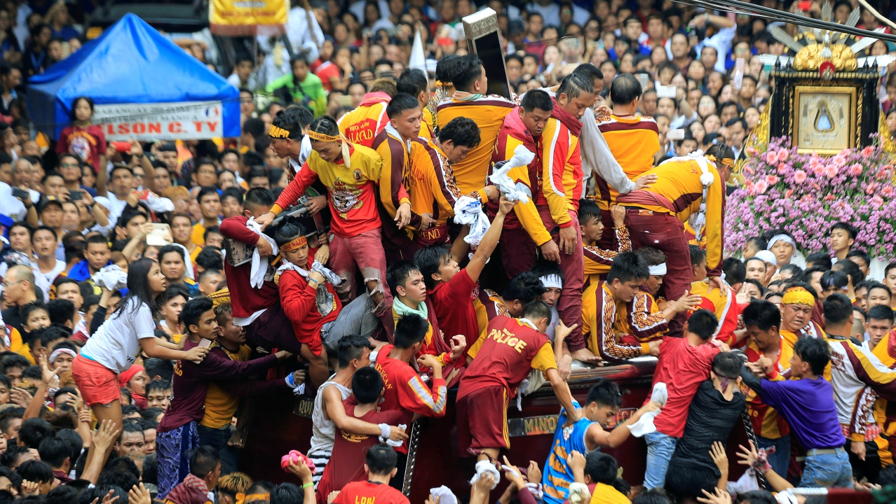 Devotees jostle while trying to reach the carriage of the image of the Black Nazarene as they participate in the annual procession at Chinatown, Metro Manila, Philippines. (Reuters)