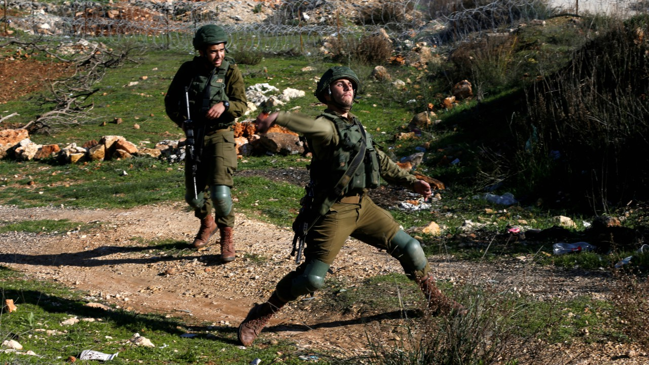 An Israeli soldier hurls a sound grenade at Palestinian protesters during clashes, near the Jewish settlement of Beit El, near the West Bank city of Ramallah. (REUTERS)