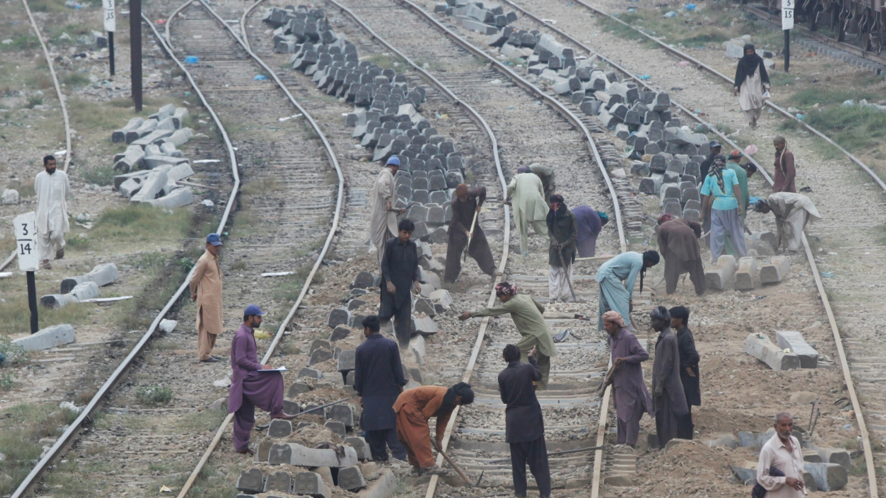 Labourers dig the ground before replacing concrete sleepers along railway tracks in Karachi, Pakistan. (Reuters)