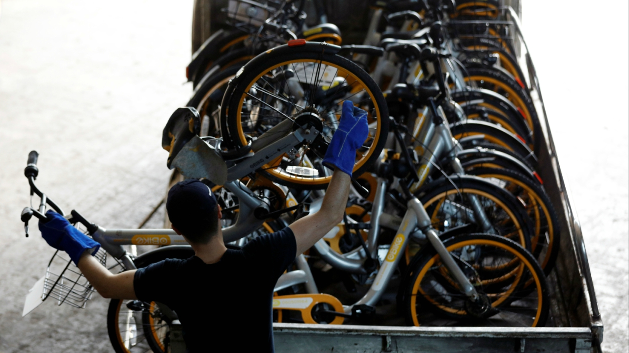Zhivko Girginov, a Bulgarian living in Singapore, returns damaged Obikes to their warehouse after gathering them around his neighbourhood in Singapore. (Reuters)
